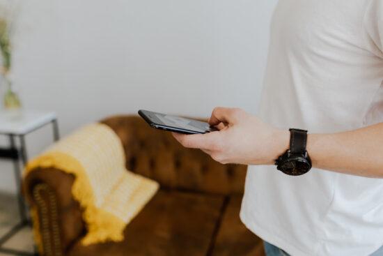 mężczyzna z zegarkiem trzymają telefon - jaki jest?